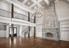 The most beautiful living room!! Floor to ceiling stone fireplace, vaulted tray ceiling, 3 tiered chandelier, iron balcony, and custom built in shelves.