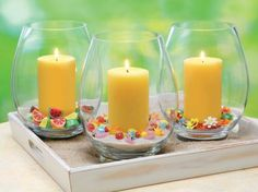 Spring, Summer or birthday party.  Another simple use of vases, available from Michael's or JoAnn stores, summer decor objects from the craft stores or dollar stores, and a simple pillar. They make great hurricane lanterns to be placed around the party area, or group them as they are here on a tray to make a lovely centerpiece. Our pillar candles are available in a quite a few styles and countless colors at BeverlyHillsCandle.com