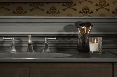Memoirs® faucet     Mixing golden-hued wood and wallpaper with soft grays and a brushed faucet finish gives the room a deep, warm glow.