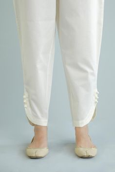 Ethnics Casual Trousers WBC101821. This tapered trouser is part of Ethnics SS20 Collecion and is made of cambric fabric in a cream colour in a plain design, curved hem with fabric buttons and fasteners, elasticated waist band with side zip and metal fastener. Pair this with any contrasting shirt or kurta.  Size & Fit: Model height is 5'5.-Model is wearing XS size Salwar Designs, Kurta Designs Women, Kurti Designs Party Wear, Stylish Dresses For Girls, Stylish Dress Designs, Salwar Pants, Kurta Neck Design, Sleeves Designs For Dresses, Nikkah Dress