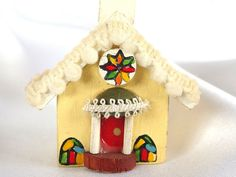 Sweet wood church is a pale yellow with colorful stained glass windows and miniature pompom trim along the eaves. This vintage Christmas