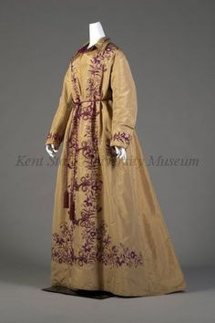 1877-1879, Dressing gown, belt. Gold silk taffeta, fuchsia embroidery. Center front opening, frog closings, patch pockets, flying bird embroidered, quilted inside. Belt: fuchsia cord with tassel.