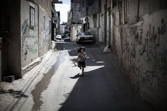 Bethlehem, West Bank: A young Palestinian girl runs through an alley at the Aida refugee camp in the West Bank
