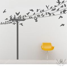 Large birds on a wire mural cut from gray matte vinyl and placed on a light gray wall behind a yellow modern stool. The mural features a power line and many different birds either flying or perched on the power line.