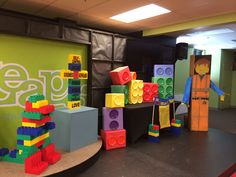 Lego stage set design. Wrapped boxes with colored paper and stuck colored paper plates. Lego guy was created from a cardboard box with poster boards used for arms. Actual blocks are from amazon and were about $150 for off brand.