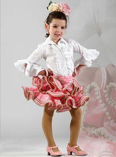 Faldas flamencas Zingara para niña de color rosa con lunares blancos con dos volantes con subida lateral y en la cintura con una pasamanería, cada volante viene acompañado de encaje de bolillos de color marrón. Puedes completar tus faldas flamencas con la blusa flamenca niña Tamara de color blanco con cuello de pico, mangas por encima del codo con dos volantes. #faldasrocieras #faldasflamencas  #conjuntoflamenco…