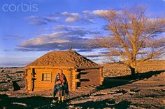A Navajo woman in front if her hogan home in Nazlini.