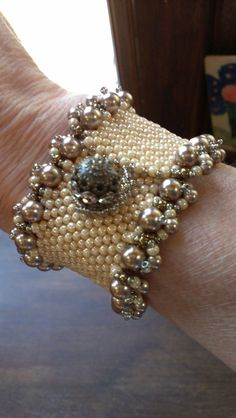 At this time, this piece is a custom order. This gorgeous antiqued ivory peyote-stitched bracelet, embellished with varying sizes of champagne