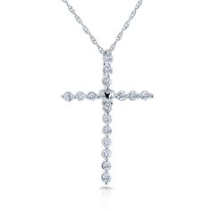 The lustrous design of this heart-warming cross pendant promotes 16 round diamonds, each expertly set in a quality prong setting. The pendant is embellished with a sweet small heart in the center, whi