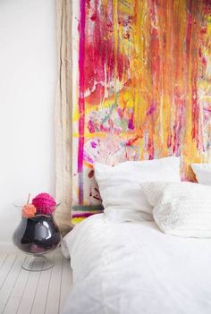 Eclectic bed on floor with painted fabric as a faux headboard