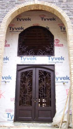 Wrought iron double entry door and transom with custom branch scroll work.