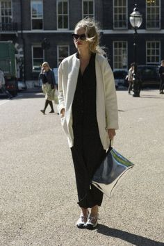 All black with an oversized white coat and a silver metallic oversized clutch