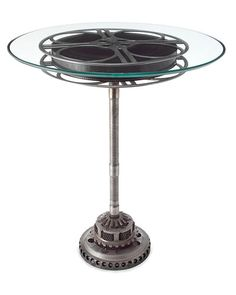 Bring the big screen to your home or office with this one-of-a-kind table made with an original aluminum 35mm film reel from the 1930s. Sandwiched between two sheets of glass and offset by a steel base made with salvaged gear parts, this unique side table is sure to draw a huge audience. Handmade in the USA.