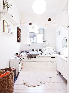 Bright and white children's bedroom with under bed storage.