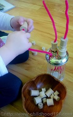 stringing spools on pipe cleaners and Parmesan jar