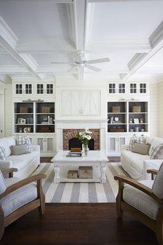 Built-ins with darker paint color behind. Tv hidden behind doors above fireplace. Love it!