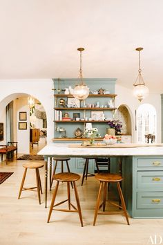 Elson's favorite ceramics by Astier de Villatte fill the shelves in her open kitchen, with cabinets painted Sherwin-Williams Underseas green | archdigest.com