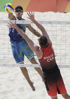 With flair, Olympic beach volleyball is underway   -    Brazi's Bruno Oscar Schmidt, top, hits over Canada's Josh Binstock during a men's beach volleyball match at the 2016 Summer Olympics in Rio de Janeiro, Brazil, Saturday, Aug. 6, 2016. (AP Photo/Marcio Jose Sanchez)