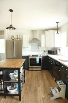 A mostly white kitchen, but so much more! Those two-tone painted cabinets are the perfect modern farmhouse look! Rustic metal hanging pendant lights, dark navy kitchen cabinets, chimney hood fan, and new vinyl plank flooring in french oak.