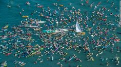 Surfers and rowers gather around a Hobie Cat catamaran off Doheny State Beach in Dana Point, California, on Friday, April 18, to celebrate t...