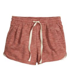 Short shorts in sweatshirt fabric. Elasticized drawstring waistband, side pockets, and pleats at front.
