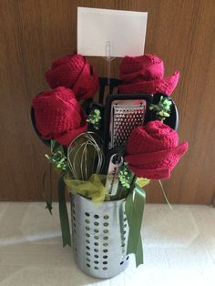 An easy and clever way to put together a wedding gift. The roses are made of towels, floral tape and BBQ skewer sticks. Different green ribbons give color and texture for the foliage. White floral ribbon is used for accents and looks like baby's breath.