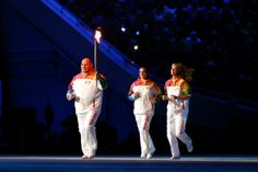 Alexandr Karelin (L) carries the Olympic torch as Elena Isinbaeva (C) and Maria Sharapova follow during the Opening Ceremony of the Sochi 20...
