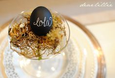 chalkboard painted easter eggs... i would get a bunch of wooden eggs to paint with pastel chalk paint and reuse them every year for name cards!