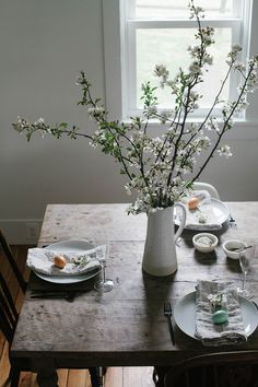 A simple Easter brunch tablescape and Easter brunch menu. Table inspiration for Easter. Simple blooming branches and wooden egg decor. Rustic dining room table.
