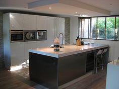 De afzuigkap bij deze design keuken is ingebouwd in het verlaagde plafond gedeelte.