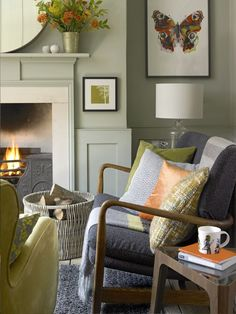 A comfy sofa in a textured fabric, colourful cushions and framed prints bring a scheme of soft greys to life. Photography: David Brittain