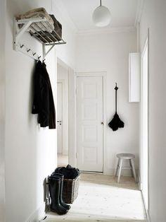 tronco de madeira rústico com ganchos para pendurar caasacos e bolsas na escada
