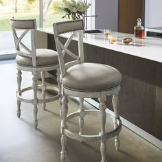 The universally appealing shapes of X's and O's are brought together in our Griffith X-Back Swivel Barstool. The circular seat juxtaposes beautifully against the strong lines of the X-back and the sumptuously padded curves, upholstered in easy-care linen or top-grain leather, are echoed in the turned hardwood legs. Smoothly swivels 180.Handcrafted of solid hardwood, with artistically turned legs Seat and backrest are upholstered in easy-care linen and detailed with nailhead trimFootre...