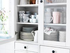 IKEA Österreich, Inspiration, Küche, Hol dir doch eine Tasse; HEMNES Vitrine mit 4 Schubladen weiß mit viel Geschirr, u. a. IKEA 365+ Espressotassen mit Untertasse weiß, TILLBAKA Becher elfenbeinweiß, POKAL Becher rosa, POKAL Gläser aus Klarglas, UNGDOM Becher in verschiedenen Mustern weiß/schwarz und ARV Teller elfenbeinweiß