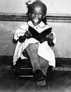 Adorably happy African American girl reading her book. Louisville, Kentucky, February 19, 1936. By George Goodman.
