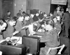Correspondents at the Ministry of Information, London, busy typing their first invasion stories on June 6, 1944. (Planet News Archive/SSPL/G...