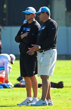 Carolina Panthers offensive coordinator Mike Shula, left, and head coach Ron Rivera, right, talk during practice on Monday, August 31, 2015.