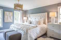 Restful white and blue bedroom boasts slate blue walls framing a white tufted wingback bed dressed in a white diamond quilt topped with a silver and gold quilt, white diamond shams, and basketweave pillows.