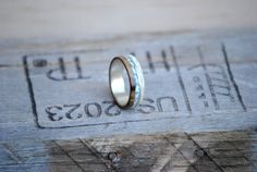 This listing includes a Men or Womens Wedding band with Silver, Walnut, Dominican Republic Larimar Stone, and Antler Inlay Please send us a message with your desired Ring Size.  We love to hear your ideas. Please message us with custom ring ideas, or if you want anything special included/changed in this ring. Remember that we do different metals for the inner band. This ring can come with either STAINLESS STEEL, TITANIUM, TUNGSTEN, SILVER, YELLOW GOLD, WHITE GOLD, or ROSE GOLD  We make all…