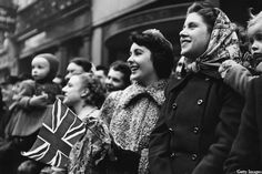 November 1948: Seventeen year old Elizabeth Taylor, back in London for the first time since she was three, waves a union jack at the Lord Mayor's Show.