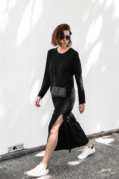 Street style look com blusa e saia preta com fenda e tênis preto.