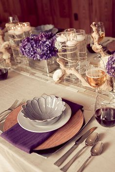 great colors and tablescape (wood, mirrors, petals, and purple). The centerpieces were created in mirrored square vessels filled with vibrant purple hydrangea. The table design also featured grape wood branches accented with balsa wood flowers. Slim cylinders with floating candles were banded with twine and accented with a rhinestone studded sunburst brooch.