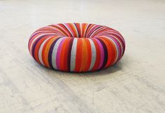 Drops Pouf consists of an inner tube wrapped in colourful ribbons of recycled textiles used for upholstery. The pouf is inspired by the art of tassel-making.