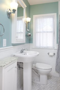 """The owners of this small NE Minneapolis bathroom not only wanted an update, but also challenged Castle with the need for additional storage space. A new petite pedestal sink, dual flush toilet, bathtub, glass hardware and sleek chrome plumbing fixtures and accessories were incorporated and beautiful 2"""" marble hex tile was installed on the floor. The custom glass countertop provides a unique but still functional surface for the daily morning routine."""