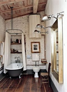 Rustic bathroom with a claw foot tub, industrial lights, and worn hardwood floors