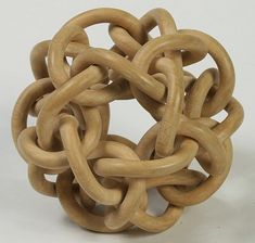 Even harder, here are six interlinked paths forming a tangle with dodecahedral symmetry.  It is carved from a solid block, and the individual parts are just free to wiggle a bit.