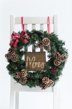 A Christmas wreath with a red plaid bow and a mini sign is the perfect chair décor for newlyweds. Christmas Wedding Centerpieces, Christmas Wedding Decorations, Wedding Wreaths, Festival Decorations, Floral Centerpieces, Christmas Themes, Diy Wedding, Christmas Wreaths, Wedding Ideas