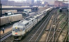 The Lake Shore Limited - New York Central E7A #4024, and its E7B mate, bring their very long train into Chicago's La Salle Street Station during May of 1964.