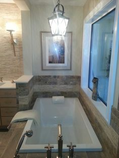 Pewter travertine marble accent surrounding the bath tub, designed and installed by Andres Silva, EXPERTILE. ..