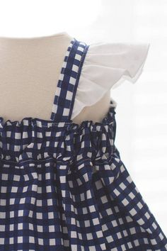 This cute little navy bluegingham dress is charming and has a lovely vintage feel. Adorned with white eyelet lace that is ruffled along the shoulder straps, and a large white bow that is sure to turn some heads. The back is elasaticized and the straps include two buttons for easy